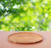 Пустой круглый деревянный поднос на таблице над предпосылкой дерева нерезкости Стоковое Изображение RF
