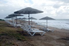 Пустой пляж на взморье в конце сезона курорта с много пустых loungers солнца Стоковые Фотографии RF