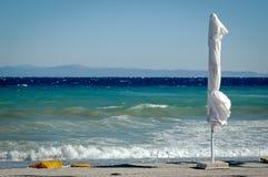 Пустой пляж с белыми зонтиком и волнами Стоковые Фотографии RF