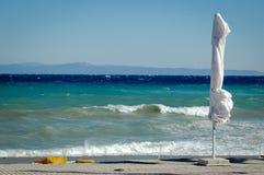 Пустой пляж с белыми зонтиком и волнами Стоковые Изображения