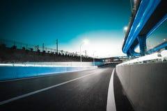 Пустой пол дороги с мостом виадука города ночи неоновых свет стоковое изображение