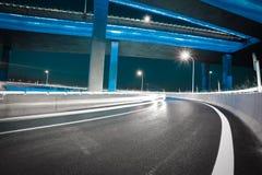 Пустой пол дороги с мостом виадука города ночи неоновых свет стоковое фото