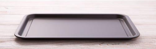 Пустой поднос выпечки для пиццы на деревянном столе изолировал близко вверх по квадрату взгляд сверху Насмешка вверх для дизайна стоковые изображения