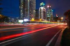 Пустой пол дорожного покрытия с современными предпосылками архитектуры ориентир ориентира города сцены ночи стоковое фото rf