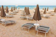 Пустой пляж с loungers и закрытыми парасолями Стоковое Фото