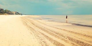 Пустой пляж Jurmala с сиротливой диаграммой девушки - ретро фильтром Стоковое Фото