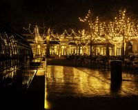 Пустой ресторан ночи, серия таблиц и стулья без одного, волшебные fairy света на деревьях любят торжество рождества Стоковое Изображение RF