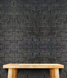 Пустой современный деревянный стол с ногой на черной кирпичной стене, шаблоне Стоковая Фотография RF