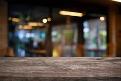 Пустой темный деревянный стол перед конспектом запачкал backg bokeh стоковая фотография