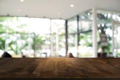 Пустой темный деревянный стол перед предпосылкой запачканной конспектом стоковая фотография rf