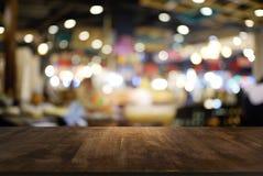 Пустой темный деревянный стол перед предпосылкой запачканной конспектом стоковое изображение rf