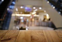 Пустой темный деревянный стол перед предпосылкой запачканной конспектом стоковые фотографии rf