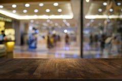 Пустой темный деревянный стол перед предпосылкой запачканной конспектом стоковая фотография