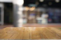 Пустой темный деревянный стол перед предпосылкой запачканной конспектом стоковое фото
