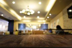 Пустой темный деревянный стол перед предпосылкой запачканной конспектом стоковое изображение