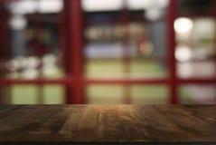 Пустой темный деревянный стол перед предпосылкой запачканной конспектом стоковые фото