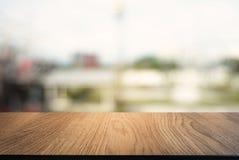 Пустой темный деревянный стол перед предпосылкой запачканной конспектом стоковые изображения rf