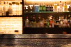 Пустой темный деревянный счетчик бара с бутылками предпосылки нерезкости re стоковое изображение