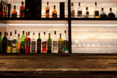 Пустой темный деревянный счетчик бара с бутылками предпосылки нерезкости стоковая фотография rf