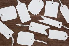 Пустой ярлык бирок белой бумаги на деревянной предпосылке Стоковое Изображение RF