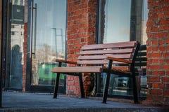 Пустой woden стенд около больших окон и кирпичной стены магазина Солнечный вечер стоковые изображения