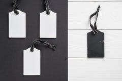 Пустые белые бирки в ряд на белой и черной деревянной предпосылке Взгляд сверху насмешка вверх по образцу Пустой ценник на деревя стоковые изображения