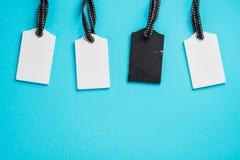 Пустые белые и черные бирки в ряд на голубой предпосылке Взгляд сверху насмешка вверх по образцу пустой ценник Дизайн для ходя по стоковое фото