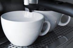 Пустые белые керамические чашки в машине кофе эспрессо Стоковые Изображения RF