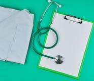 пустые белые листы и медицинский стетоскоп на зеленой предпосылке стоковые изображения