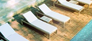 Пустые белые loungers приближают к бассейну на модель-макете поверхности кирпича Стоковые Фото