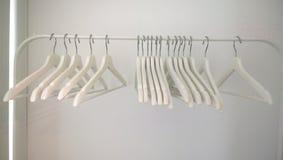 Пустые белые вешалки одежд висят на кронштейне Стоковые Фото