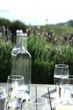 Пустые бутылки и стекла на деревянном столе Стоковая Фотография