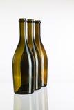 Пустые бутылки вина на стеклянном столе Стоковые Фотографии RF