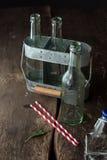 Пустые бутылки в подносе на деревянном столе Стоковые Фотографии RF