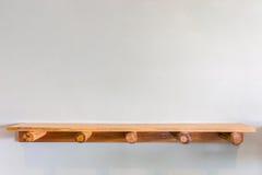 Пустые верхние деревянные полки на стене белого цемента Стоковые Фото