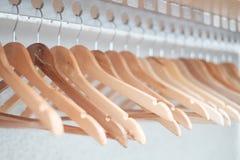 Пустые вешалки одежд выровнялись вверх в комнате стоковое изображение rf