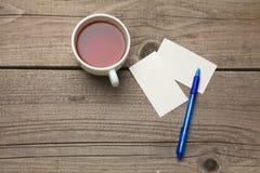 Пустые визитные карточки с чашкой ручки и чая дальше Стоковое фото RF