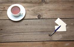 Пустые визитные карточки с чашкой ручки и чая дальше Стоковая Фотография
