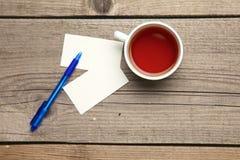 Пустые визитные карточки с чашкой ручки и чая на деревянной таблице офиса Стоковые Фото