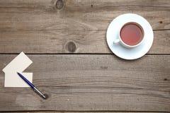 Пустые визитные карточки с чашкой ручки и чая на деревянной таблице офиса Стоковое фото RF