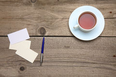 Пустые визитные карточки с чашкой ручки и чая на деревянной таблице офиса Стоковая Фотография