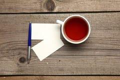 Пустые визитные карточки с чашкой ручки и чая на деревянной таблице офиса Стоковое Фото