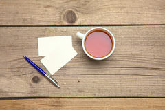 Пустые визитные карточки с чашкой ручки и чая на деревянной таблице офиса Стоковое Изображение