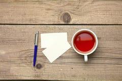 Пустые визитные карточки с чашкой ручки и чая на деревянной таблице офиса Стоковые Изображения