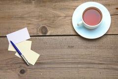 Пустые визитные карточки с чашкой ручки и чая на деревянной таблице офиса Стоковая Фотография RF