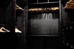 Пустые деревянные вешалки одежд вися в шкафе и бросая глубоких тенях стоковая фотография