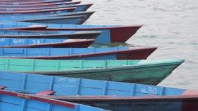 Пустые деревянные шлюпки поставленные на якорь на пристани пошатывая в волнах сток-видео