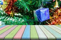 Пустые деревянный стол или планка с красочной коробкой подарка на xmas или рождественской елке на предпосылке Стоковые Изображения