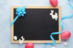 Пустые доска и украшение пасхи с зайчиком и розовыми яйцами стоковые фотографии rf