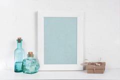 Пустые деревянные белые рамка, бутылки синего стекла и подарочная коробка Стоковая Фотография